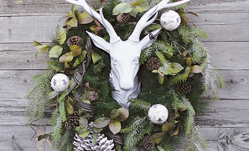 Stag head with decorated greenery wreath