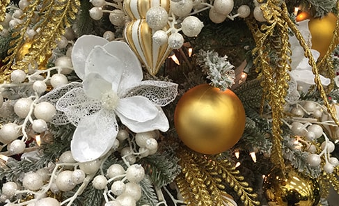 artificial white christmas flower with gold ornaments in a christmas tree
