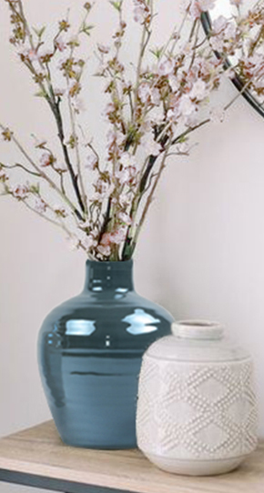 Teal vase with cherry blossoms on wood table