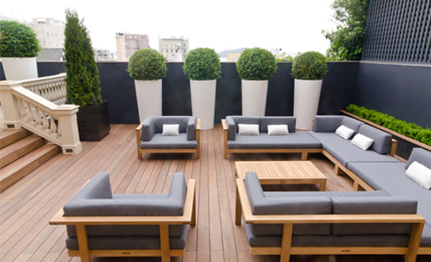 luxe outdoor patio space with couches and artificial boxwood